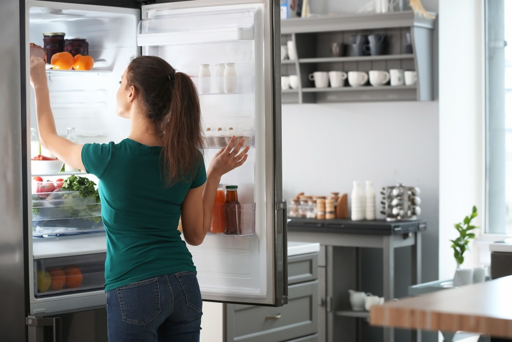 woman taking something out of the fridge