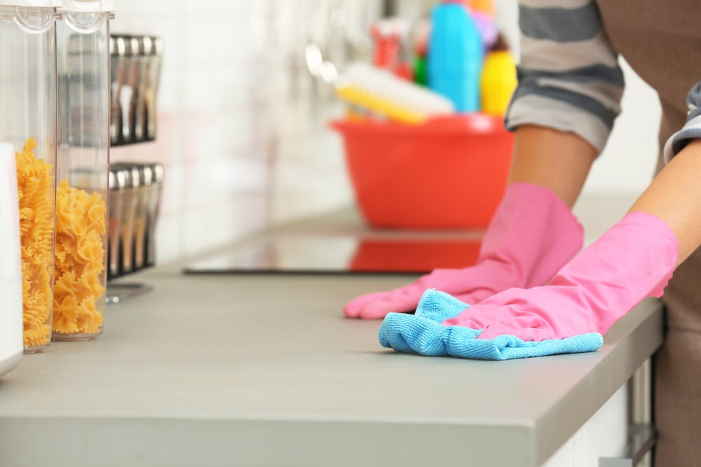 person cleaning kitchen counter